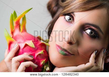Headshot brunette, dark mystique look and green lipstick, holding up pink pitaya fruit, looking into camera.