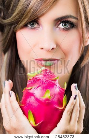 Headshot brunette, dark mystique look and green lipstick, holding up pink pitaya fruit with both hands facing camera.