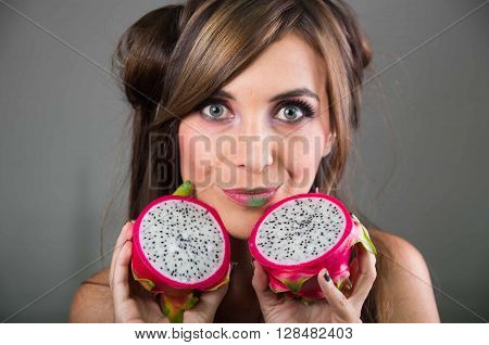 Headshot brunette, dark mystique look and green lipstick, holding up two open halfs of pink pitaya fruit with both hands facing camera.