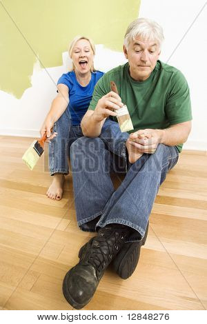 Middle-aged couple in front of wall they are painting green while male tries to paint women's toenails with paintbrush.