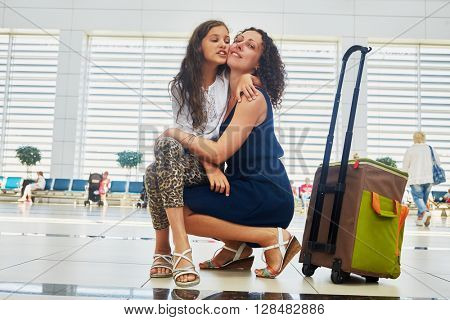 Mother and daughter in waiting hall at airport.