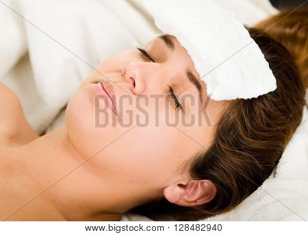 Closeup headshot young woman lying down with eyes closed, white towel pad resting on forehead.