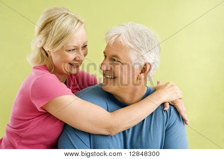 Portrait of smiling middle-aged couple in front of green wall hugging.