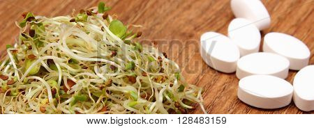 Alfalfa and radish sprouts with tablets supplements on wooden surface choice between healthy eating and pills healthy lifestyle food and nutrition