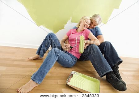 Portrait of happy adult couple sitting in front of half-painted wall with paint supplies laughing.