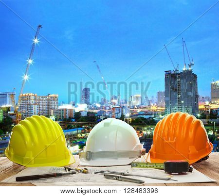 Engineer Working Table With Hard Hat Plan And Writing Tool Against Beautiful Lighting And Urban Buil