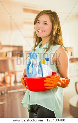 Pretty young woman holding red bucket of cleaning products and smiling to camera, housecleaning concept.