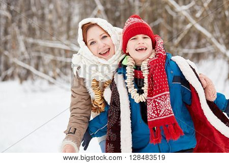 Teenage girl with shawl on head and boy stand laughing in winter park.