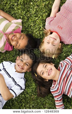 Children lying in clover with heads together. Vertically framed shot.