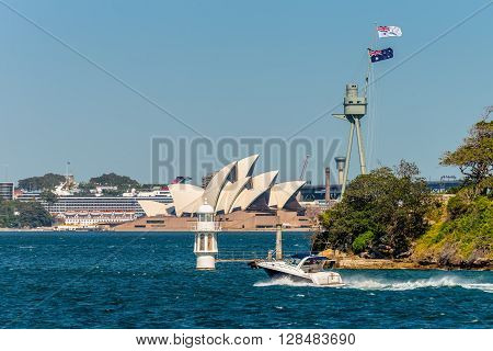 Sydney Australia - November 9 2014: The Sydney Opera from ferry passing Bradleys Head lighthouse and HMAS Sydney memorial mast Sydney NSW Australia.