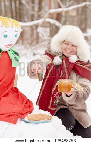 Smiling woman dressed in fur jacket and hat pours honey onto pancake near stuffed Maslenitsa in winter park.