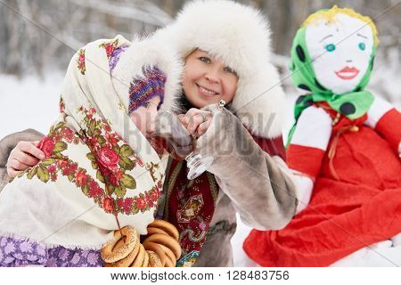 Mother dressed in fur jacket and hat gives hot drink little daughter near stuffed Maslenitsa in winter park.