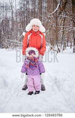 Mother with little daughter stand in snowy winter park.