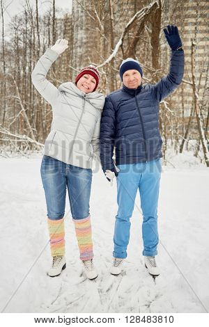 Smiling woman and man on skates stand on ice pathway in park waving hands.