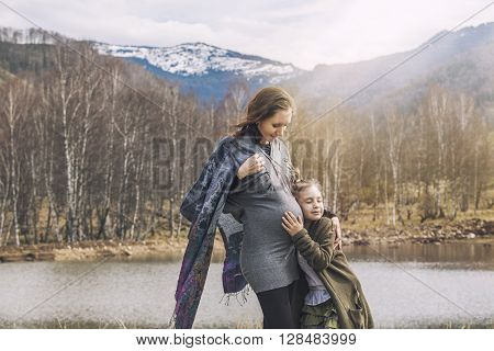 Young Beautiful Pregnant Woman And Her Baby Daughter Smiling Woman In A Landscape Nature