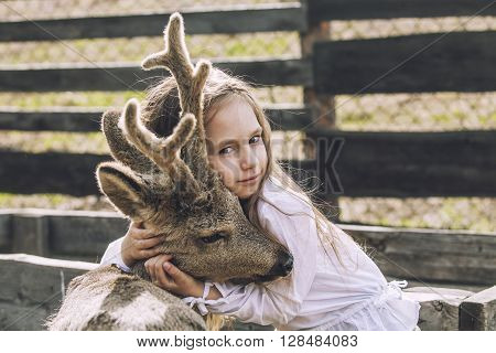 Beautiful Little Girl Hugging Animal Roe Deer In The Sunshine