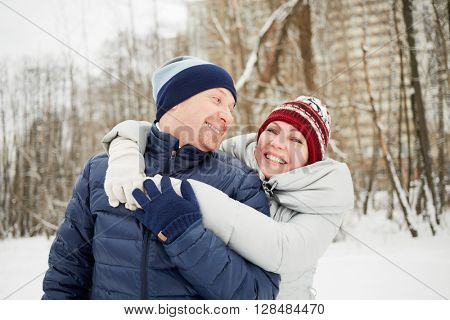 Half-length portrait of embracing smiling man and woman in winter park.