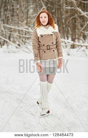 Teenage girl with braces on teeth stands on skates on ice pathway in park.