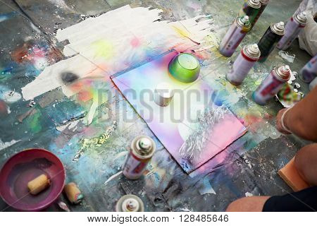 Young man draws a picture with spray paints.