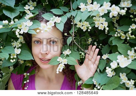 Young woman looks out from blooming jasmine bush in park.