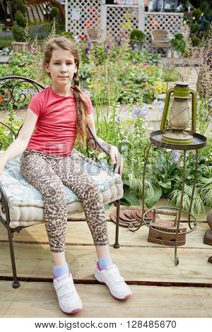 Little girl sits on old-fashioned metal armchair near old lamp against blooming park.