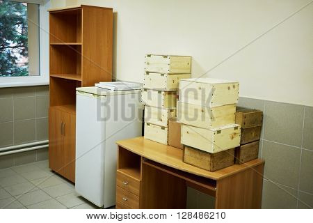Service room with refrigerator, table, and wooden boxes.