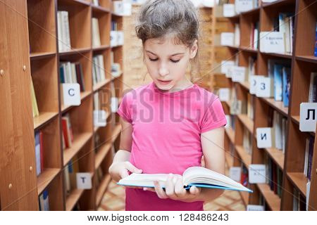 Teenage girl stands between bookcases in library and reads book.