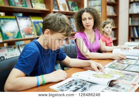 Mother and two children sit and read books in reading room of children library, focus on mother.