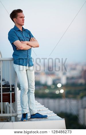 Young man in denim clothes stands crossing arms on chest on the roof leaning his back to the railing.