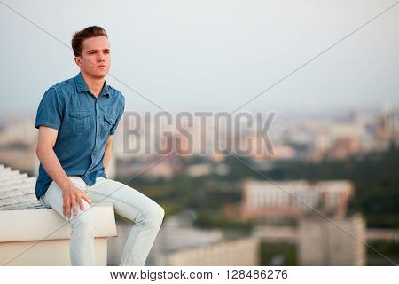 Young man in denim clothes sits on the edge of the building roof.