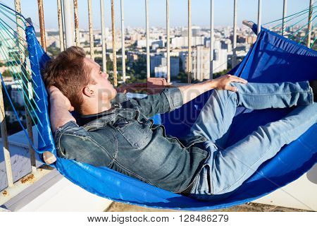 Young man in denim clothes naps in hammock attached to building roof fencing.