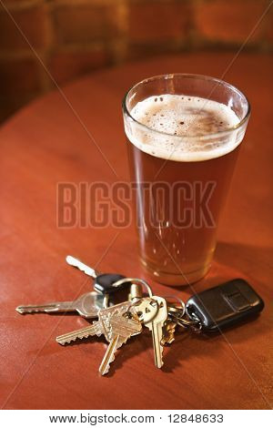 Car keys lying next to a full glass of beer.  Vertical shot.