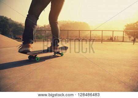 young skateboarding woman riding skateboard at skatepark