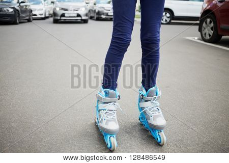Legs of woman on rollers standing on the carriage way with cars behind.