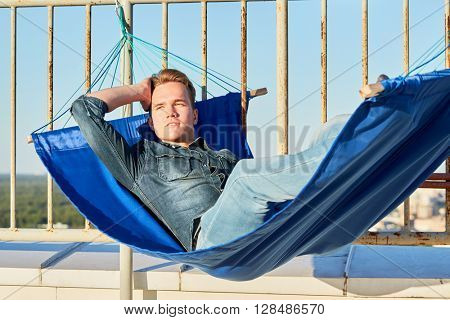Young man in denim clothes lies in hammock mounted to fencing of building roof.