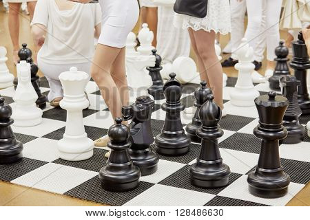 Large floor-stand chess figures and female legs among them.