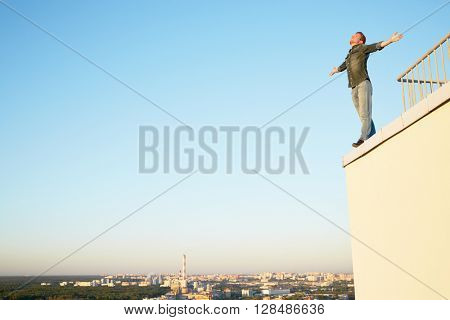 Young man in denim clothes stands on the edge of the building roof outstretching arms to sides against blue sky.