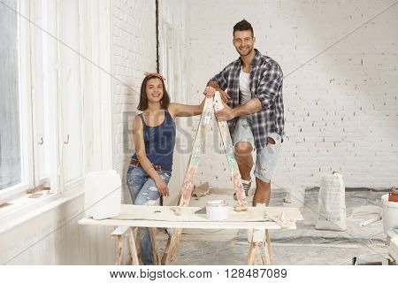 Happy young couple smiling, standing on ladder at home under construction.