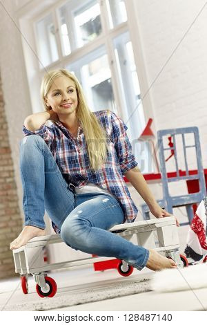 Young blonde woman sitting in retro home, smiling, looking away.