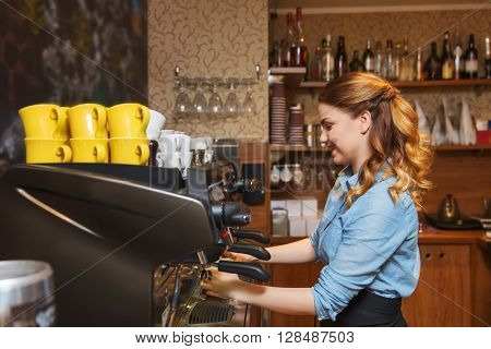 equipment, coffee shop, people and technology concept - barista woman making coffee by espresso machine at cafe bar or restaurant kitchen