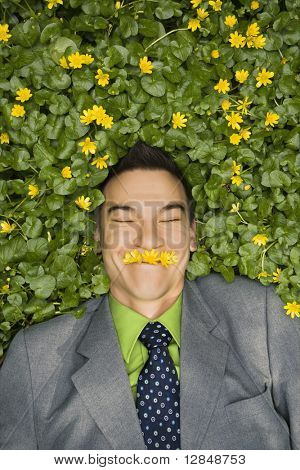 Young smiling businessman relaxing in a flower patch wearing flowers over his mouth like a mustache.