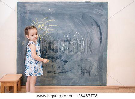 Full length cute little girl standing near blackboard