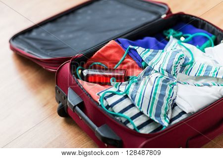 summer vacation, travel, tourism and objects concept - close up of travel bag with beach clothes, sunglasses and sunscreen
