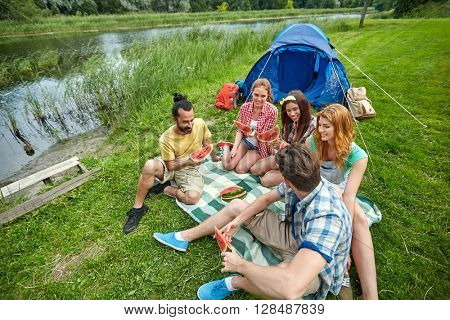 travel, tourism, hike, picnic and people concept - group of happy friends with tent eating watermelon at camping
