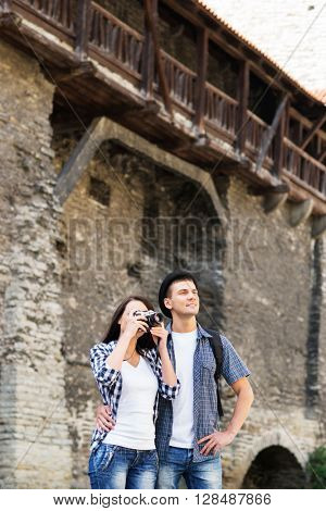 Young beautiful traveling couple with an old medieval building on the background.