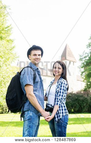 Beautiful traveling couple holding hands in summer park with medieval tower on the background.