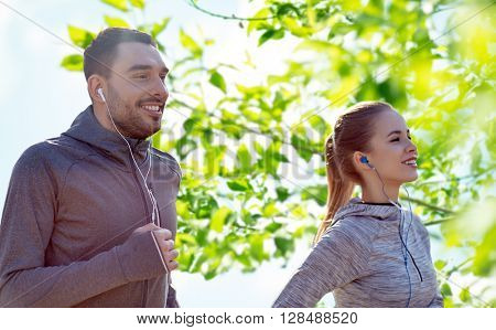 fitness, sport, people, technology and lifestyle concept - happy couple running and listening to music in earphones over green natural background