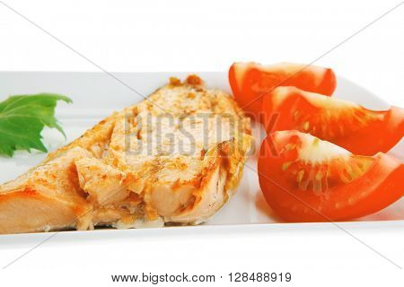 soft goat feta salt cheese with grilled sea salmon tomatoes and green lettuce salad served on white china plate isolated on white background