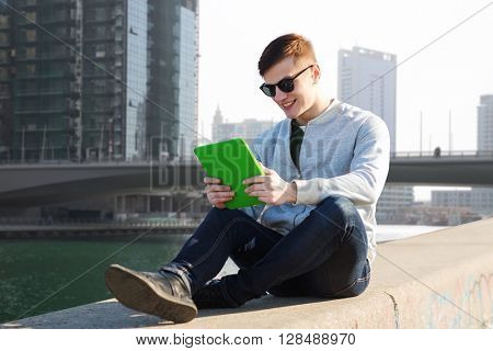 technology, travel, tourism and people concept - smiling young man or teenage boy with tablet pc computers over dubai city street background