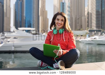 technology, travel, tourism, music and people concept - smiling young woman or teenage girl with tablet pc computer and headphones over dubai city street and boats in harbor background
